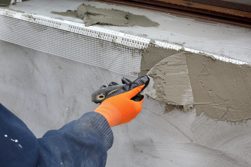 Рабочий наносит изолирующую смесь шпателем на стену
