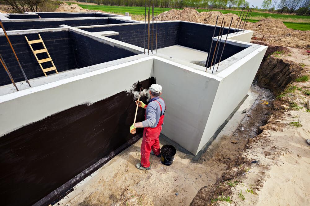 Рабочий наносит гидроизоляцию на стены