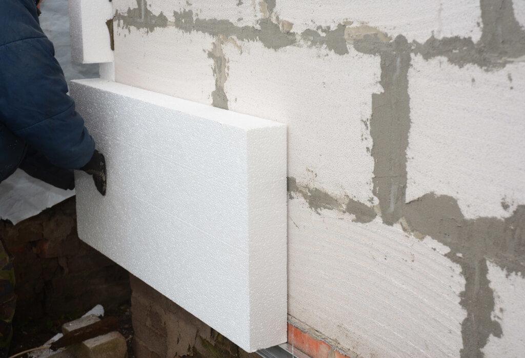 Рабочий крепит панель из пеноплекса к стене