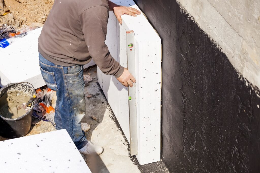 Строитель отмеряет высоту блока из пенопласта
