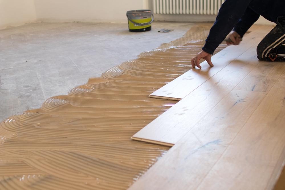 Рабочий укладывает планки напольного покрытия