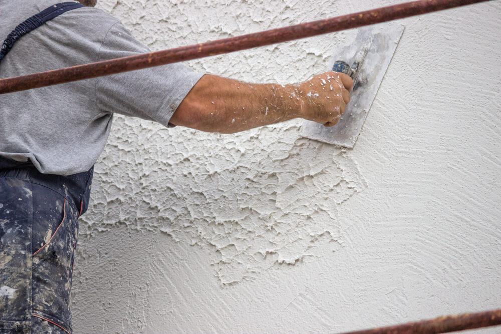 Мужчина наносит декоративную штукатурку на стену