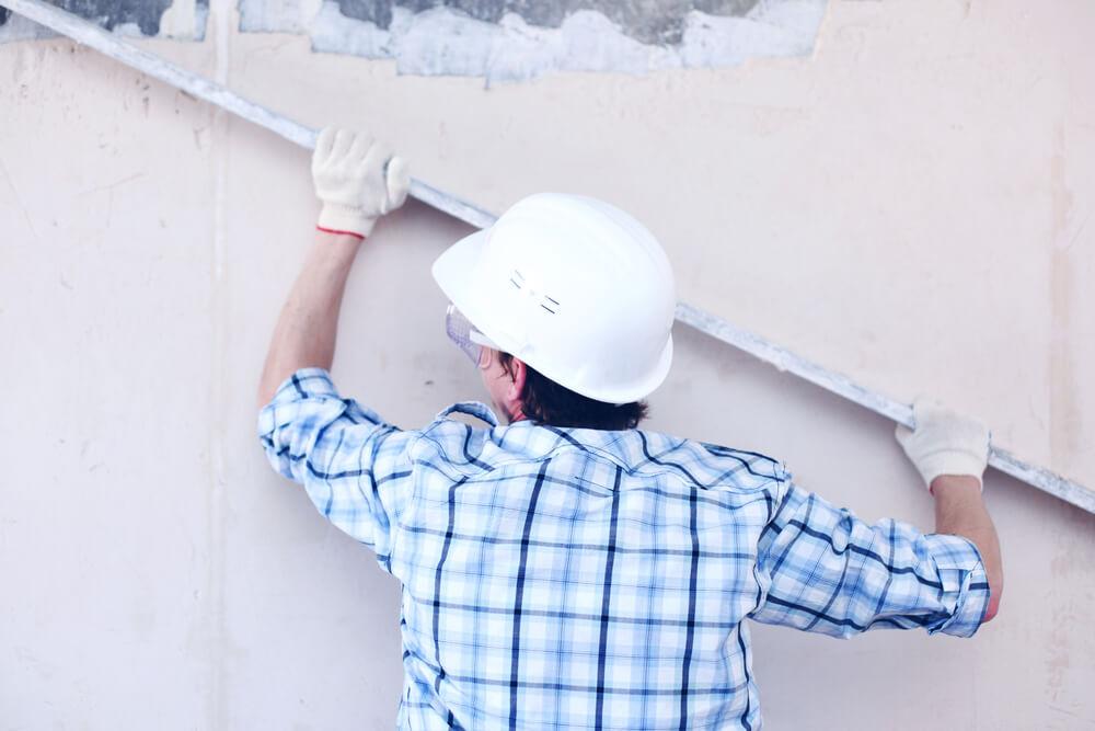 Рабочий выравнивает стену правилом