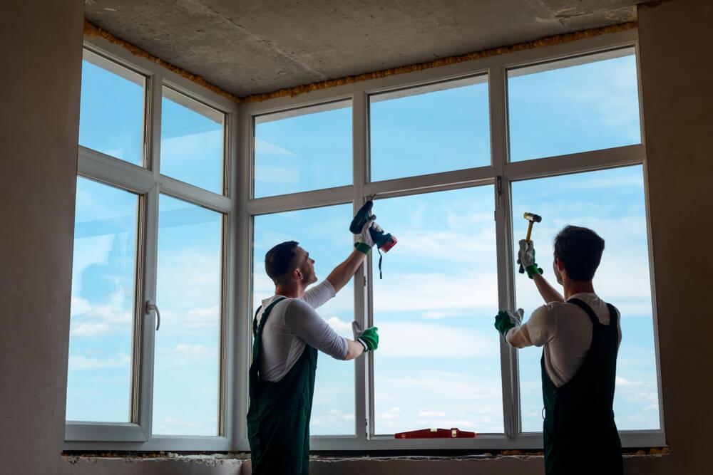 Строители устанавливают пластиковое окно