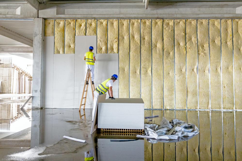 Строители устанавливают панели на шумоизолированные стены многоэтажки